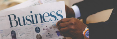 Photo of a man reading the business section of the newspaper.