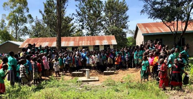 School children gather at the site of the new well